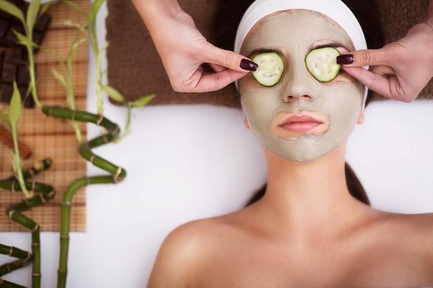 La bella giovane donna sta ottenendo la maschera facciale dell'argilla alla stazione termale
