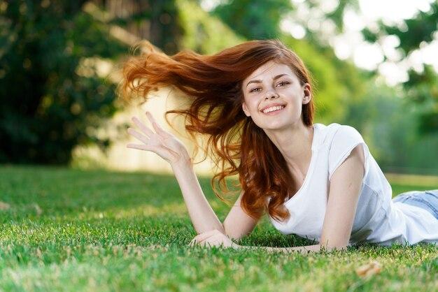 La bella giovane donna sta riposando in erba verde fresca