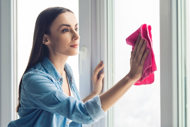 La bella giovane donna sta usando uno straccio mentre pulisce le finestre