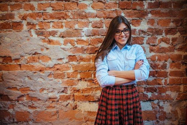 La bella giovane donna sta vicino al vecchio muro di mattoni.