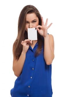 La bella giovane donna tiene la carta in bianco
