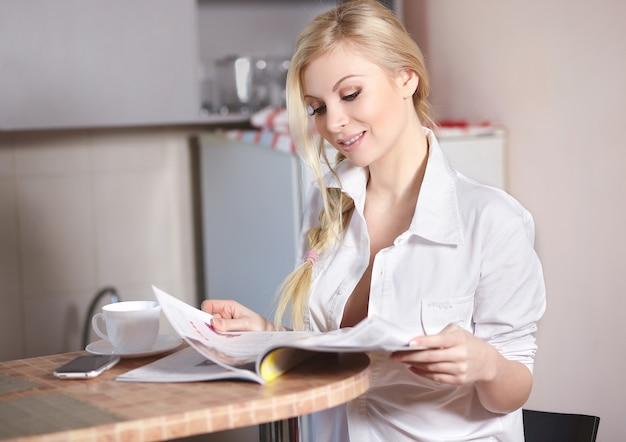 La bella giovane donna tiene la seduta in cucina e legge la rivista