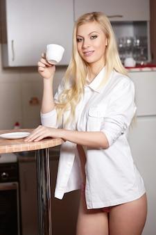 La bella giovane donna tiene una tazza di caffè sulla cucina