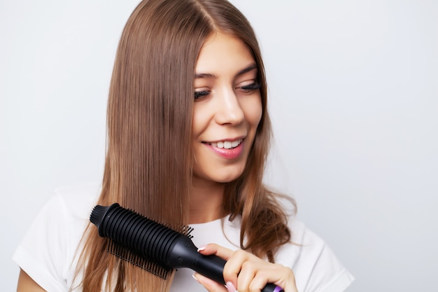 La bella giovane donna usa una piastra per capelli per creare uno stile bellissimo