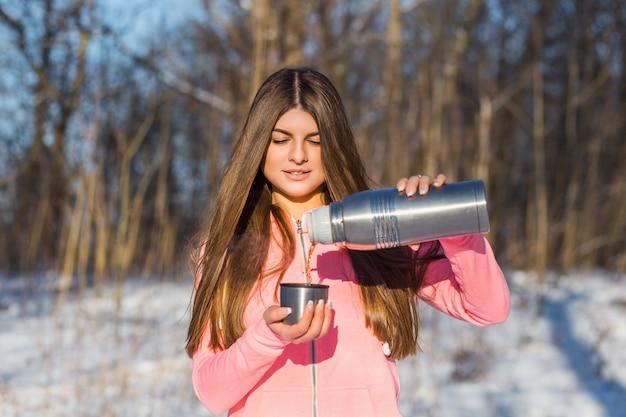 La bella giovane donna versa il tè