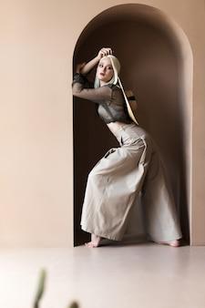 La bella giovane modella bionda sta posando in cappello di paglia e camicetta trasparente verde