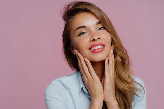 La bella giovane modella femmina tocca delicatamente il mento con entrambe le mani, sorride delicatamente, ha un aspetto tenero