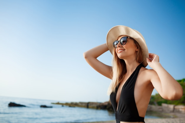 La bella giovane ragazza allegra in cappello ed occhiali da sole riposa alla spiaggia di mattina