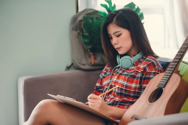 La bella giovane ragazza asiatica dei pantaloni a vita bassa che gioca la chitarra a casa per si rilassa