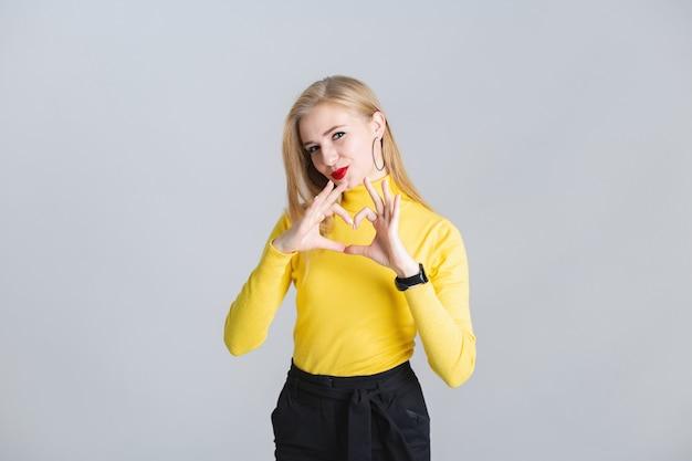 La bella giovane ragazza bionda mostra il cuore di gesto con le sue mani