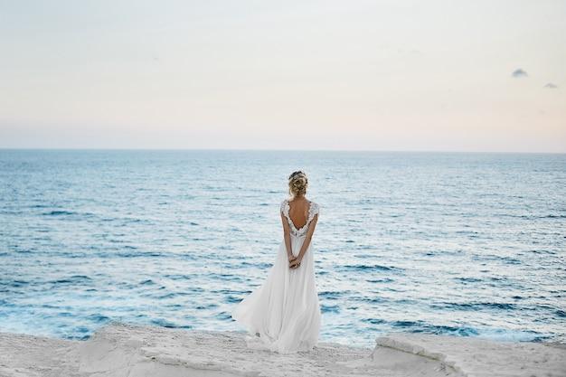 La bella giovane ragazza di modello bionda in vestito bianco sta indietro e guarda il mare