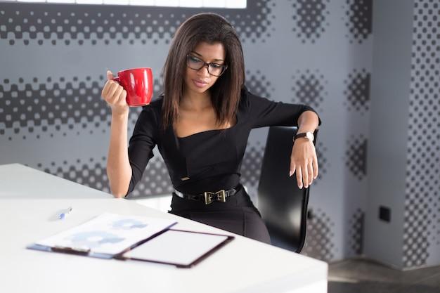 La bella giovane signora di affari in forte suite nera si siede al tavolo dell'ufficio, tiene la tazza rossa