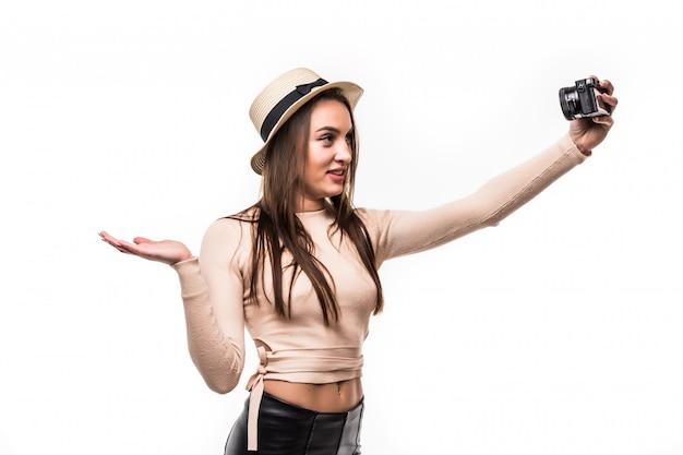 La bella giovane signora in maglietta luminosa e cappello fa selfie sulla retrocamera isolata su bianco