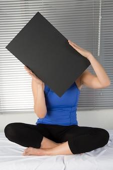 La bella giovane signora sta sostenendo un tabellone per le affissioni nero in bianco con lo spazio della copia