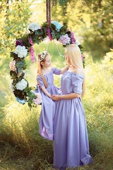 La bella madre con capelli biondi lunghi che posano e che giocano con sua figlia in lavanda simile si veste nel parco all'aperto