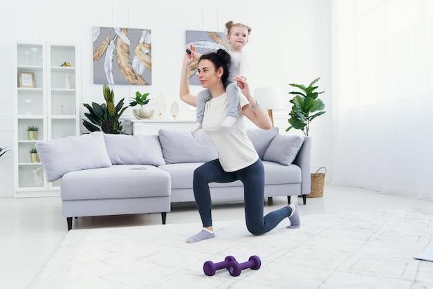 La bella mamma e la piccola figlia affascinante stanno sorridendo mentre fanno gli esercizi di forma fisica insieme a casa.