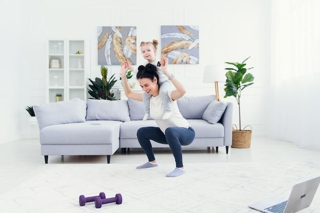 La bella mamma e la piccola figlia stanno sorridendo mentre fanno gli esercizi di forma fisica insieme a casa