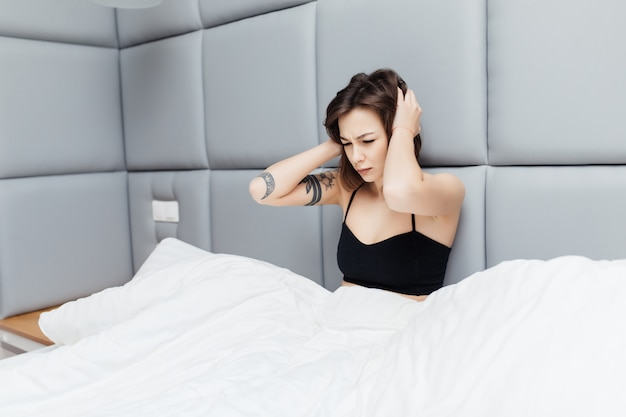 La bella mora mostra uno sguardo malsano la mattina dopo il sonno nel suo ampio letto