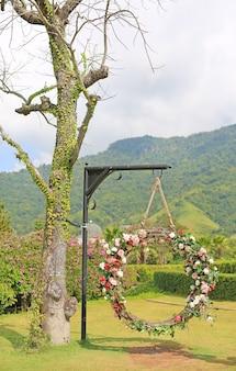 La bella oscillazione del cesto delle nozze decorate con le rose variopinte fiorisce nel natu
