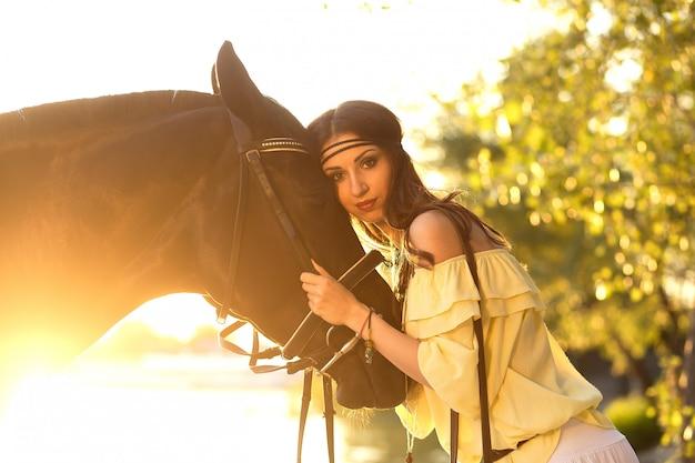 La bella ragazza abbraccia un cavallo al tramonto al sole