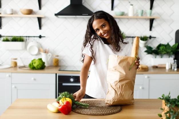 La bella ragazza afro disimballa i prodotti da un supermercato e parla al telefono