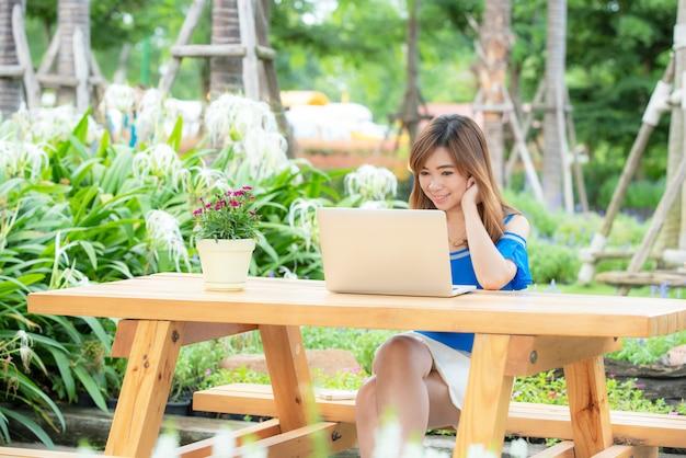 La bella ragazza asiatica celebra con il computer portatile, posa felice di successo. concetto di e-commerce, formazione universitaria, tecnologia internet o startup.