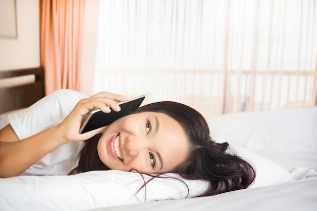 La bella ragazza asiatica che si trova sul letto che sorride facendo uso dello smartphone, la donna gode di di chiacchierare o del concetto online di compera