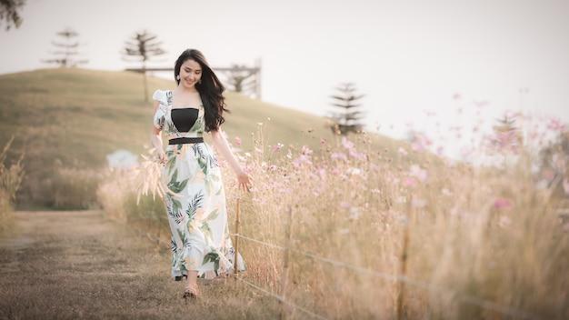 La bella ragazza asiatica delle donne che cammina e che sorride si rilassa nell'annata di stile dell'immagine del fiore del parco