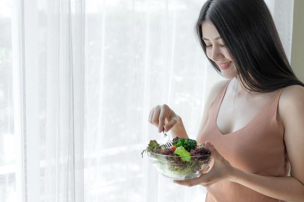 La bella ragazza asiatica di bellezza della ragazza di tatto felice mangia l'insalata fresca dell'alimento di dieta per buona salute di mattina