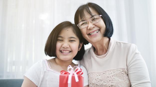 La bella ragazza asiatica offre una scatola regalo spaziale a sua nonna