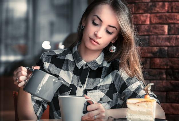 La bella ragazza beve il tè in un caffè