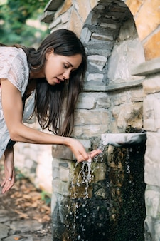 La bella, ragazza beve l'acqua di fonte all'aperto