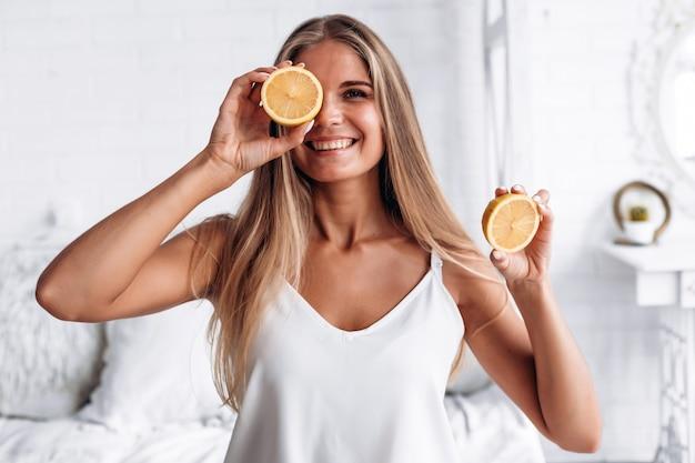 La bella ragazza bionda decide il limone in mano e chiude gli occhi