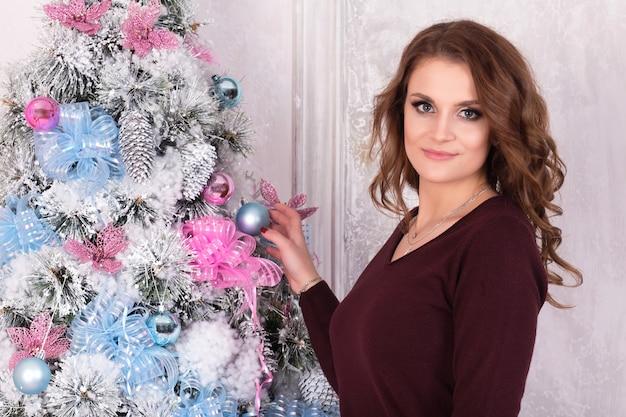 La bella ragazza castana in un maglione rosso sta vicino ad un albero nel nuovo anno e sorride e tenendo una palla