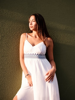 La bella ragazza castana in un vestito bianco fa una pausa la parete verde