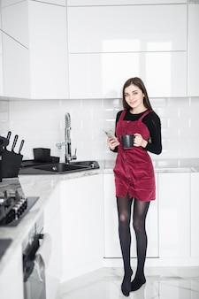 La bella ragazza castana in vestiti domestici sta usando uno smartphone e sta sorridendo mentre si sedeva nella cucina