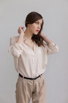 La bella ragazza caucasica con le labbra rosse in camicia beige alla moda sembra meditatamente da parte. concetto di solitudine