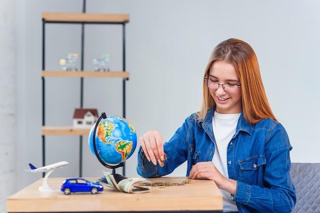 La bella ragazza caucasica conta i suoi risparmi per le vacanze straniere. la giovane donna si siede al tavolo con vaso di vetro, denaro, globo, modello di aereo aereo e auto.