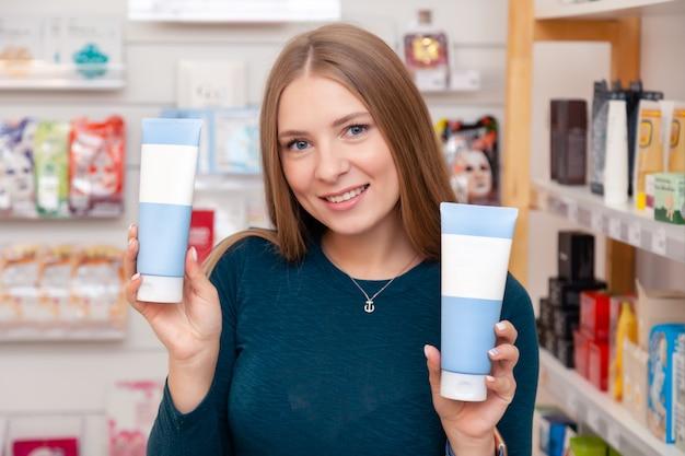 La bella ragazza caucasica cosmetologa tiene la scatola d'argento con un prodotto cosmetico senza marchio, mock up con un'etichetta vuota per aggiungere il marchio al prodotto, puoi scrivere il tuo marchio su di esso