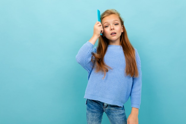 La bella ragazza caucasica dell'adolescente con capelli marroni in maglia con cappuccio blu spazzola i suoi capelli isolati su fondo blu