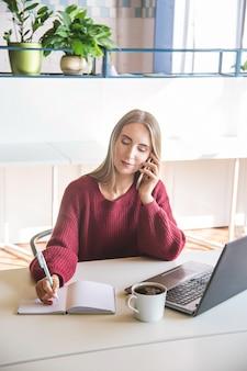 La bella ragazza caucasica parla per telefono e scrive in un taccuino nel suo luogo di lavoro.