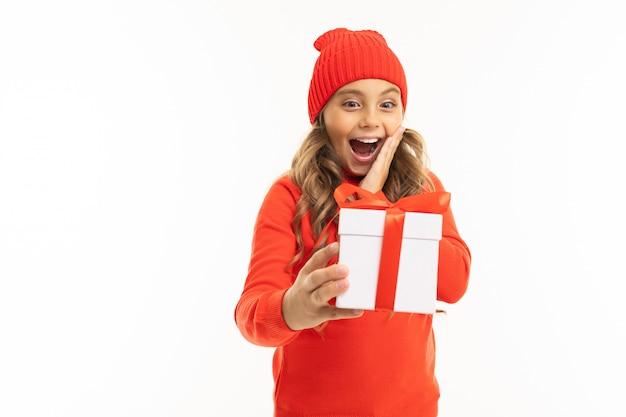 La bella ragazza caucasica tiene una scatola bianca con il regalo e ha molte emozioni isolate su bianco