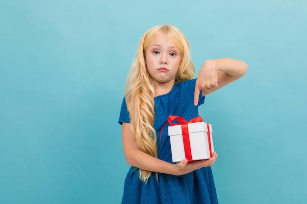 La bella ragazza caucasica tiene una scatola bianca con il regalo e ha molte emozioni isolate sul blu