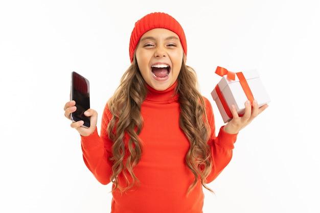 La bella ragazza caucasica tiene una scatola bianca con il regalo in una mano e uno smartphone nell'altra mano, sorride e sceglie fra esso isolato su bianco