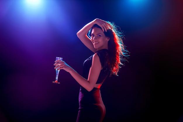 La bella ragazza che balla alla festa e beve champagne