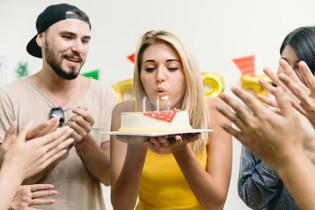 La bella ragazza che soffia la torta di compleanno alla festa con gli amici applaude la sua canzone per festeggiare il compleanno.