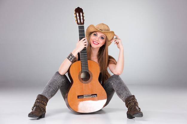 La bella ragazza con cappello da cowboy e chitarra acustica.