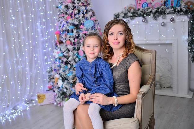 La bella ragazza con la mamma sta decorando un albero di natale in casa