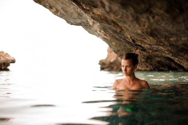 La bella ragazza con la testarossa ha legato i capelli nella caverna dell'acqua