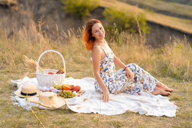 La bella ragazza dai capelli rossi gode del tramonto sulla natura. pic-nic in campo.